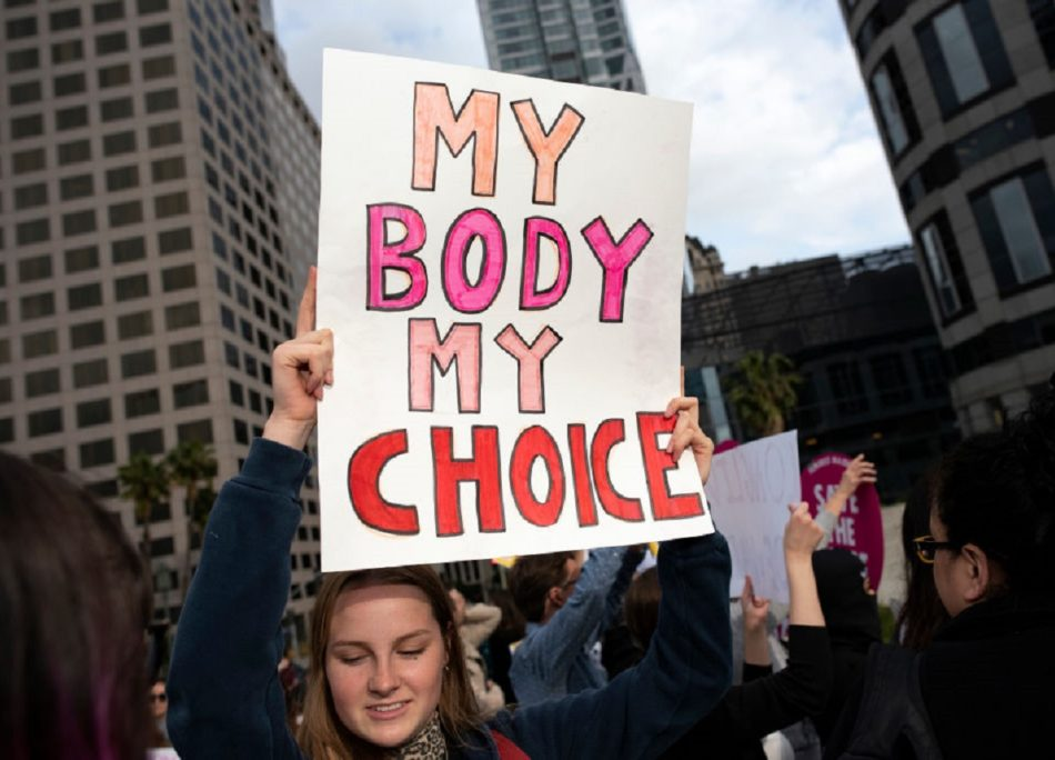 An activist seen holding a placard that says My body My